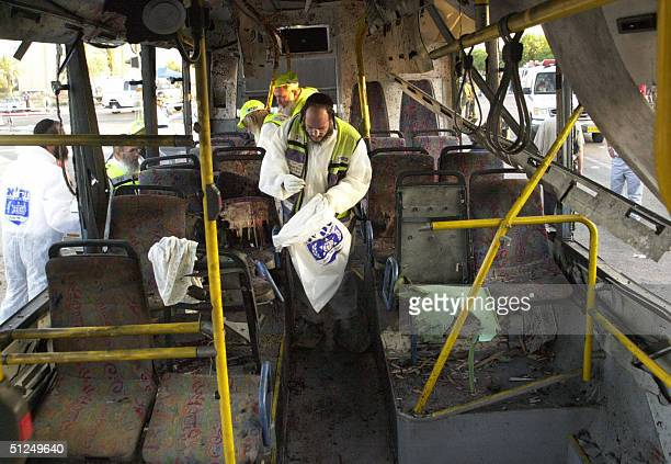Zaka emergency services volunteers collect human remains from one of the destroyed buses that were targeted by a twin suicide bombings 31 August 2004...