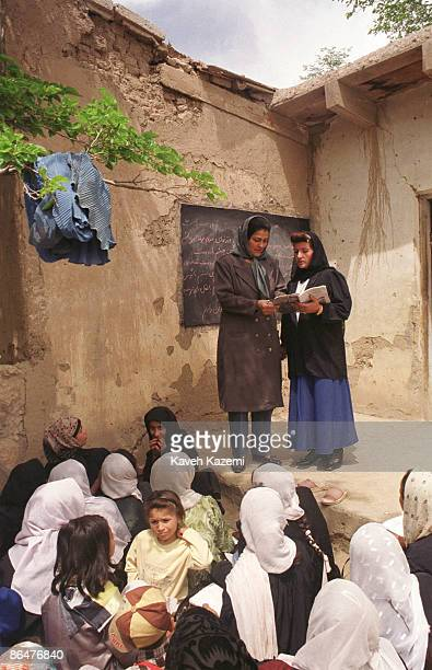 Zakia , the headmistress of a school in Panjshir Valley, Afghanistan, speaks to the teacher in an open air classroom, 22nd April 2002. The teacher's...
