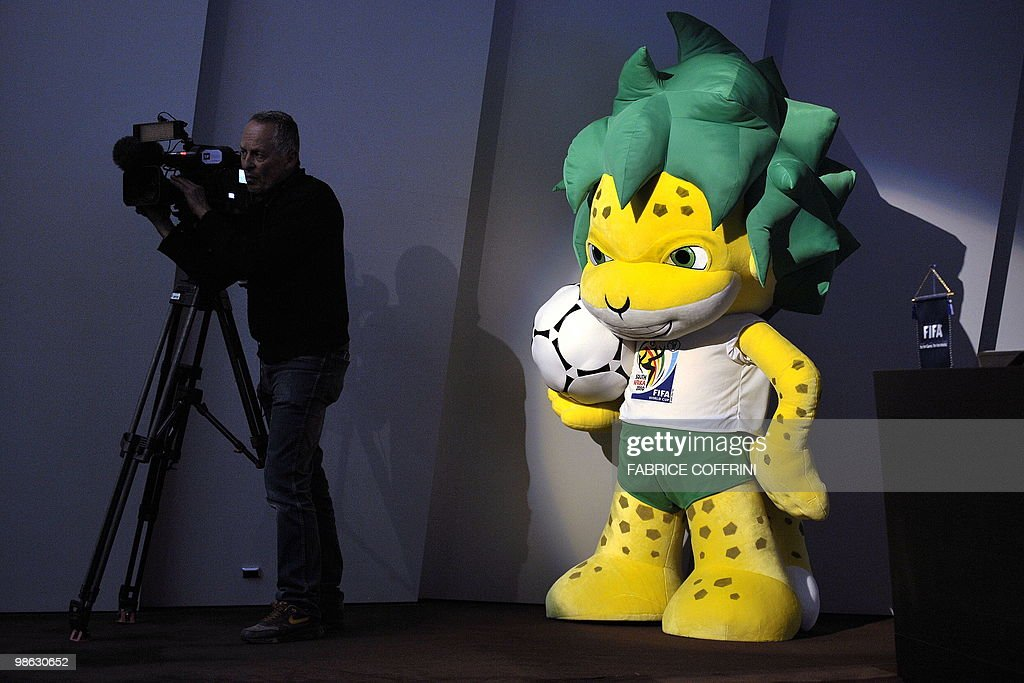 Zakumi, the FIFA 2010 World Cup mascot stands behind a TV operator during a press conference on April 23, 2010 at the football's governing body headquarters in Zurich, 48 days before the beginning of the football tournament hosted by South Africa from June 11 to Jully 11, 2010.