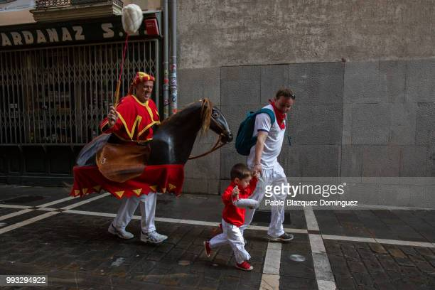 A 'Zaldiko' chases a child during the Comparsa de Gigantes y Cabezudos or Giants and Big Heads parade on the second day of the San Fermin Running of...