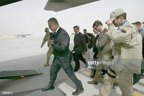Zalmy Khalilzad White House special envoy to Iraq walks towards a C130 aircraft April 15 2003 at the alUdeid air base near Doha to fly to a...