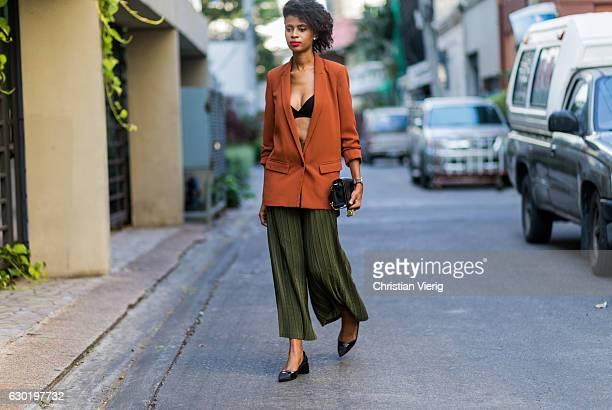 Zama is wearing an orange blazer from Mango a Zara bra green wide leg pants Zara and Zara shoes on December 17 2016 in Bangkok Thailand