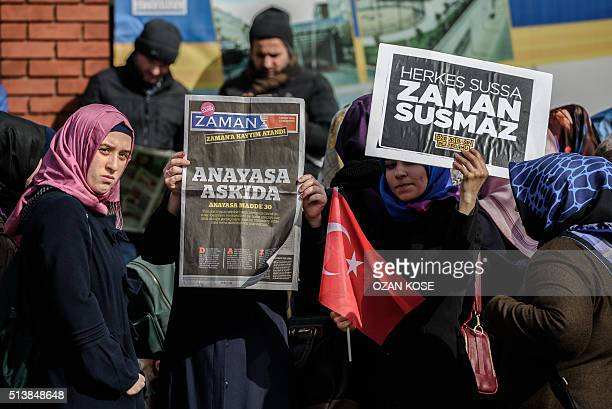 A Zaman supporter holds the latest edition of Turkish daily newspaper Zaman with the headline 'Suspended the constitution' while another holds a...