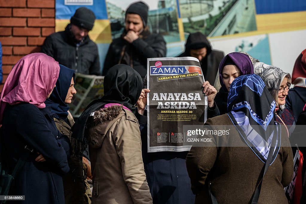 A Zaman supporter holds the latest edition of Turkish daily newspaper Zaman with the headline 'Suspended the constitution' in front of the newspaper's headquarters in Istanbul on March 5, 2016, after Turkish authorities seized the headquarters in a midnight raid. Turkish authorities on March 5 were in control of the newspaper staunchly opposed to President Recep Tayyip Erdogan after using tear gas and water cannon to seize its headquarters in a dramatic raid that raised fresh alarm over declining media freedoms. Police fired the tear gas and water cannon just before midnight at a hundreds-strong crowd that had formed outside the headquarters of the Zaman daily in Istanbul following a court order issued earlier in the day. / AFP / OZAN