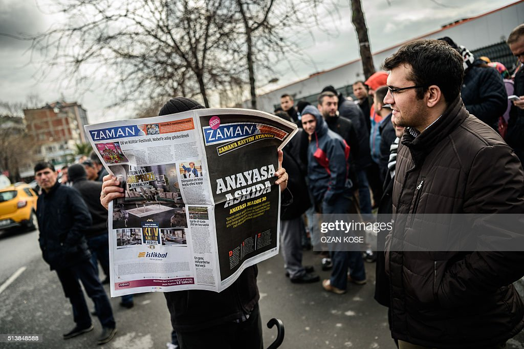 A Zaman supporter reads the latest edition of Turkish daily newspaper Zaman with the headline 'Suspended the constitution' in front of the newspaper's headquarters in Istanbul on March 5, 2016, after Turkish authorities seized the headquarters in a midnight raid. Turkish authorities on March 5 were in control of the newspaper staunchly opposed to President Recep Tayyip Erdogan after using tear gas and water cannon to seize its headquarters in a dramatic raid that raised fresh alarm over declining media freedoms. Police fired the tear gas and water cannon just before midnight at a hundreds-strong crowd that had formed outside the headquarters of the Zaman daily in Istanbul following a court order issued earlier in the day. / AFP / OZAN