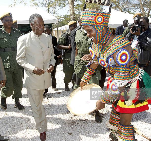 Zambia President Michael Sata joins a traditional dancer on May 17 2013 during the commissioning of the construction of Palabana University in...