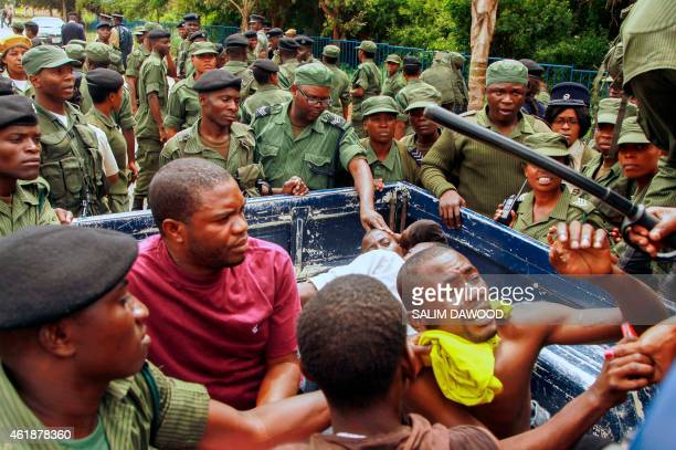 Zambian police officers apprehend supporters of the opposition United Party for National Development party outside the Presidential Election result...