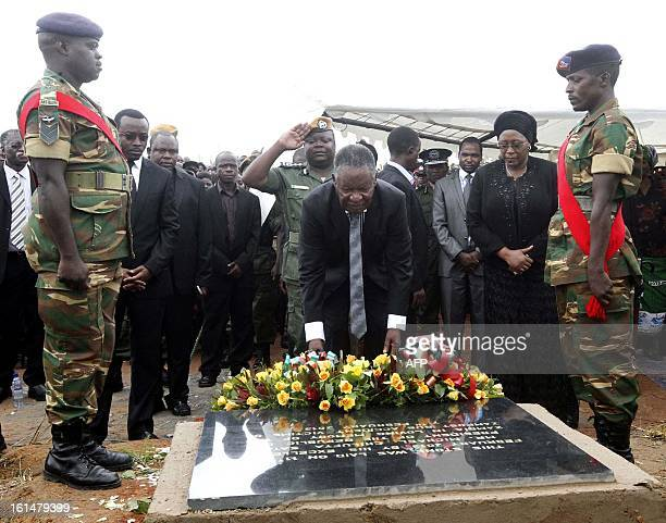 Zambian President Michael Sata flanked by his wife Dr Christine Kaseba lays a wreath on February 11 2013 at Mutengo Cemetery in Ndola where the...