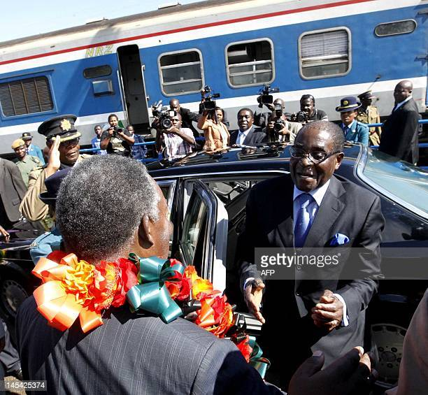 Zambian President Michael Sata welcomes his Zimbabwean counterpart Robert Mugabe to the Victoria Falls bridge on May 29 2012 for the signing ceremony...