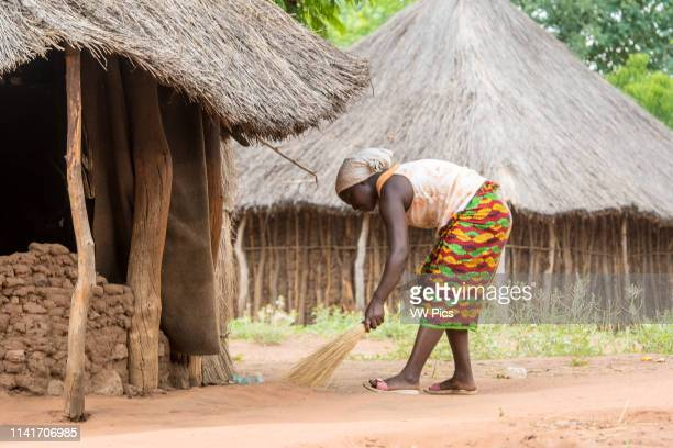 Zambian woman in traditional patterned skirt uses hand broom to sweep up litter that has been discarded onto ground Mukuni Village Zambia