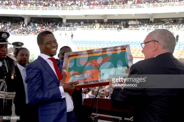 Zambia's newly elected President Edgar Lungu receives the instruments of power from acting president Guy Scott after being sworn in as Zambia's...