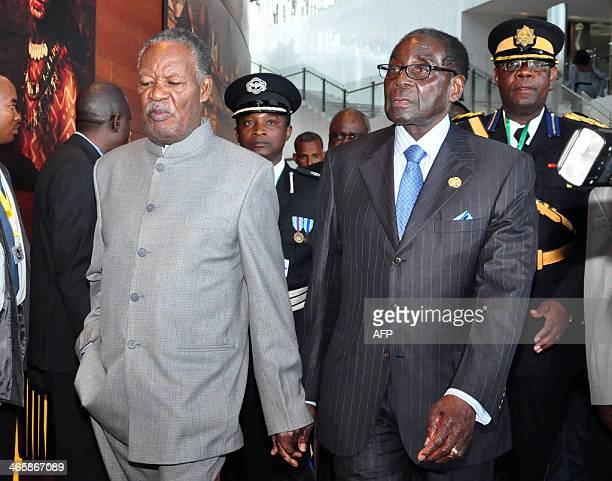 Zambia's President Michael Sata and his Zimbabwean counterpart President Robert Mugabe walk hand in hand on January 30 2014 as they arrive at the...