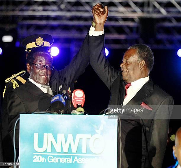Zambias President Michael Sata and Zimbabwe's President Robert Mugabe hold hands as they address United Nations World Tourism Organization delegates...