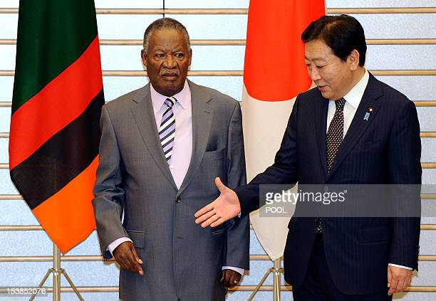 Zambia's President Michael Sata is greeted by Japanese Prime Minister Yoshihiko Noda prior to their meeting at the premier's official residence in...