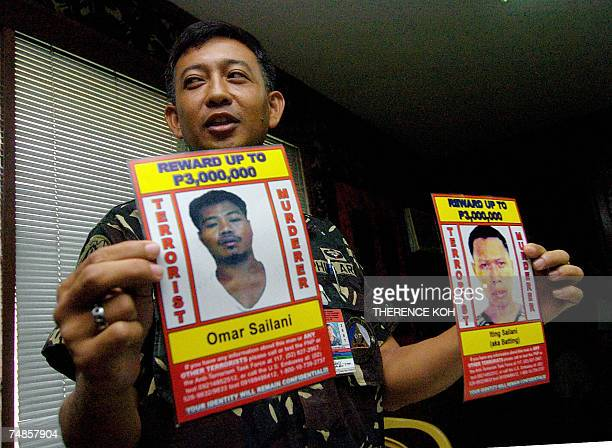 Major Eugene Batara Western Mindanao command information officer shows the wanted posters of Abu Sayyaf's Urban Terrorist Group members Omar and...