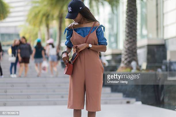 Zamzie is wearing a pastel orange jumpsuit with white cropped legs a blue denim off shoulder top a pastel orange bag and a navy new york yankees...