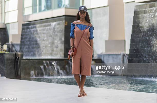 Zamzie is wearing a pastel orange jumpsuit with white cropped legs a blue denim off shoulder top a pastel orange bag sandals and a navy new york...