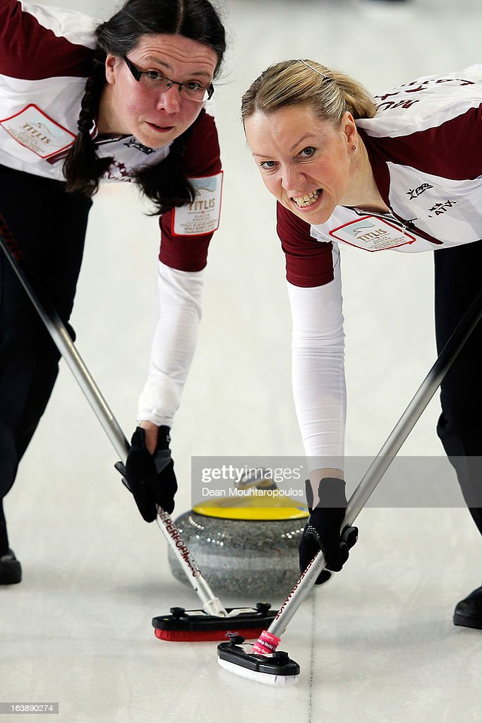 Zanda Bikse (L) and Dace Munca (R) of Latvia sweep in the match between Latvia and Japan during Day 2 of the Titlis Glacier Mountain World Women's Curling Championship at the Volvo Sports Centre on March 17, 2013 in Riga, Latvia.
