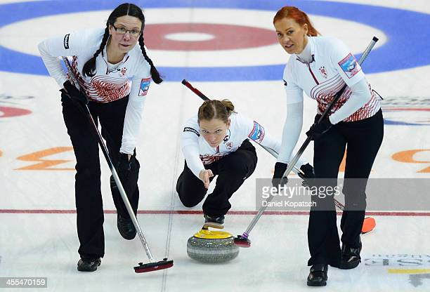 Zanda Bikshe of Latvia and teammate Una Germane sweep after Ieva Krusta throws a rock during the Olympic Qualification Tournament match between Japan...
