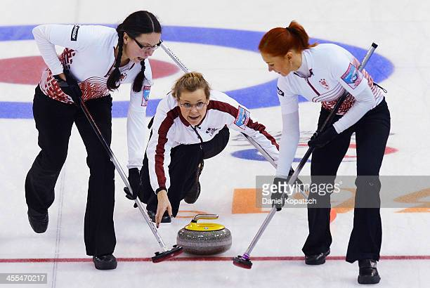 Zanda Bikshe of Latvia and teammate Una Germane sweep after Iveta StasaSarsune throws a rock during the Olympic Qualification Tournament match...