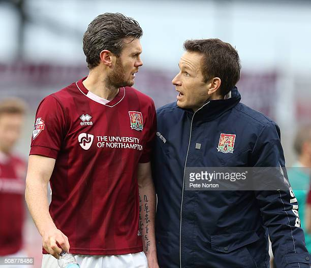 Zander Diamond of Northampton Town looks on bemused as he is helped from the pitch by Dr Andrew Odwell after a clash of heads which left him...