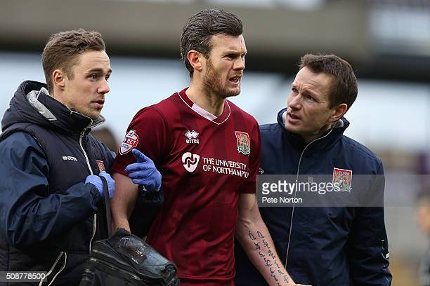 Zander Diamond of Northampton Town looks on bemused as he is helped from the pitch by physio Anders Braastad and Dr Andrew Odwell after a clash of...