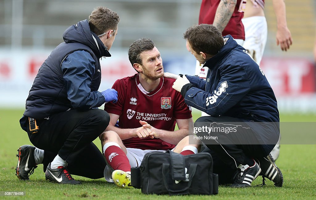 Zander Diamond of Northampton Town recieves treatment from physio Anders Braastad and Dr Andrew Odwell after a clash of heads which left him concussed during the Sky Bet League Two match between Northampton Town and York City at Sixfields Stadium on February 6, 2016 in Northampton, England.