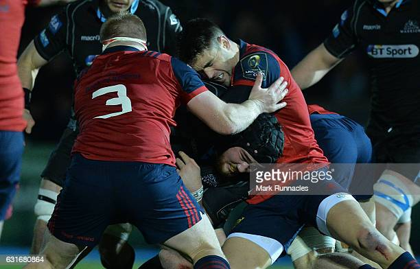 Zander Fagerson of Glasgow Warriors is tackled by Connor Murray and John Ryan of Munster Rugby during the European Rugby Champions Cup match between...