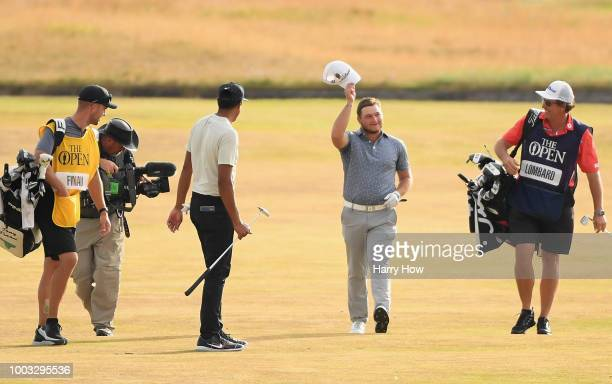 Zander Lombard of South Africa celebrates his eagle on the 18th hole with Tony Finau of the United States during the third round of the 147th Open...