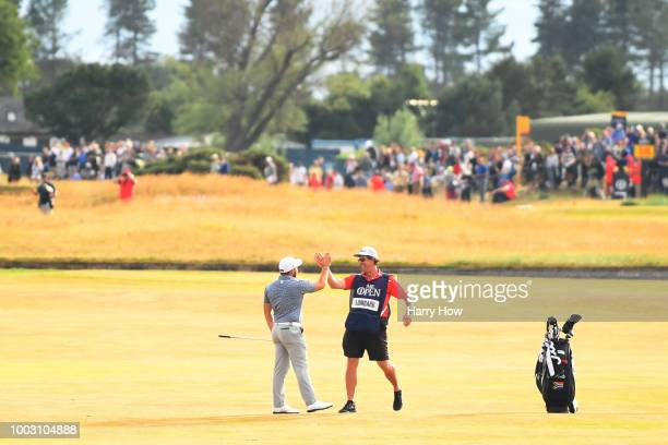 Zander Lombard of South Africa celebrates with his caddie Alan Burns after his eagle on the 18th hole during the third round of the 147th Open...