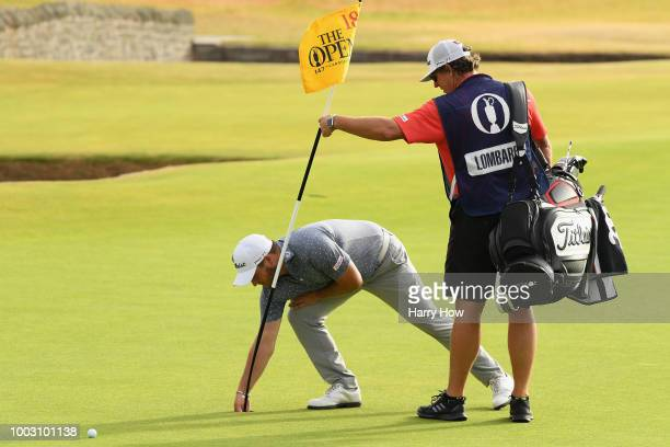 Zander Lombard of South Africa picks the ball out of the hole after his eagle on the 18th during the third round of the 147th Open Championship at...