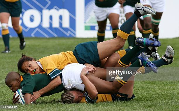 Zandile Nojoko of Team South Africa comes down on top of Ruan Sims of Team Australia while being tackled by Sims and teammate Lisa Fiaola during...
