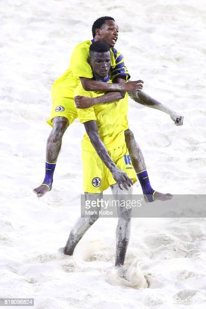 Zane Amedee of Saint Lucia celebrates with his team mate Linus Clovis of Saint Lucia scoring a goal during the Boys Beach Soccer match 4 between the...