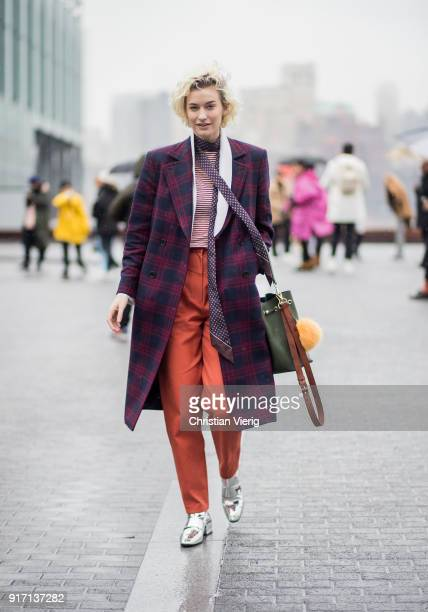 Zanita Whittington wearing plaid coat orange pants silver boots green bag seen outside Tibi on February 11 2018 in New York City