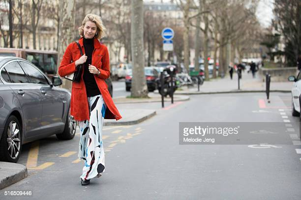 Zanita Whittington wears a red Sportmax coat and printed Acler trousers at the Ellery show at Palais de Tokyo on March 07 2016 in Paris France