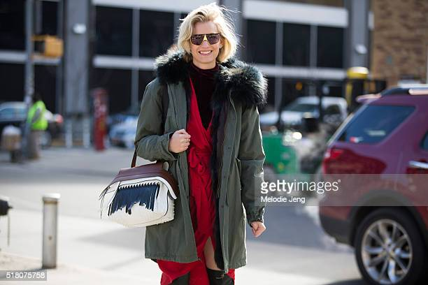 Zanita Whittington wears vintage sunglasses a Mr Mrs Italy green parka with a fur hood a red Zimmermann robestyle dress and a Tod's wave bag during...