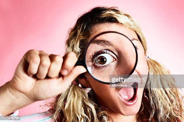 Zany blonde looks through magnifying glass with hugely enlarged eye