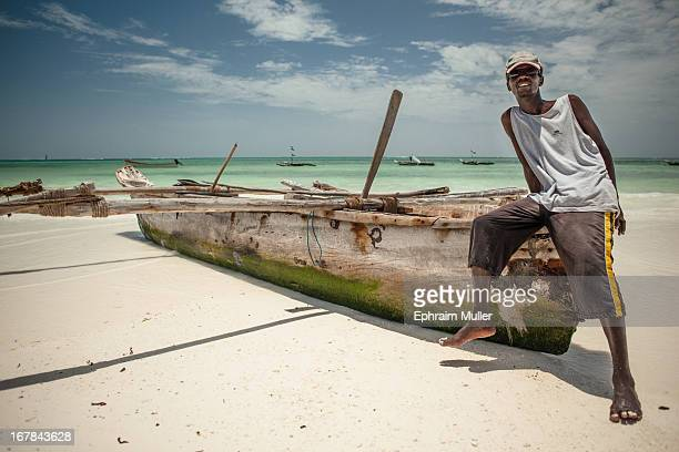 Zanzibar ferryman leaning on his Dhow attempting to coax me into a trip on his dhow so i offered him a dollar for a portrait with his boat instead