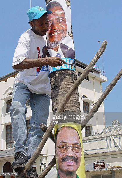 A Zanzibari glues 05 September 2005 a poster of the main opposition candidate Seif Sheriff Hamad above another of his main rival for the presidency...