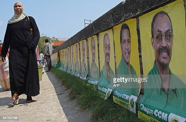 A Zanzibari woman walks 05 September 2005 along a wall covered with campaign posters of Zanzibar ruling party Chama Cha Mapinduzi presidential...