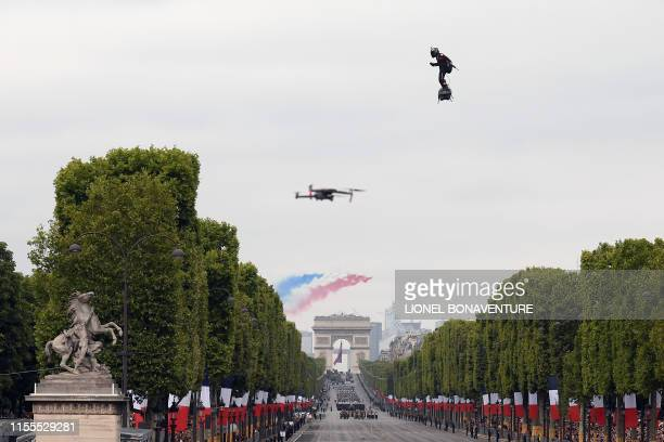 TOPSHOT Zapata CEO Franky Zapata flies a jetpowered hoverboard or Flyboard as French elite acrobatic flying team Patrouille de France flies over the...