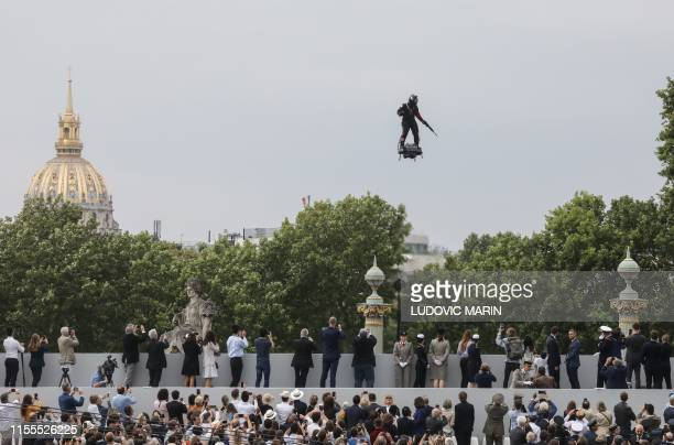 """Zapata CEO Franky Zapata flies a jet-powered hoverboard or """"Flyboard"""" prior to the Bastille Day military parade down the Champs-Elysees avenue in..."""