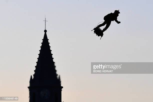 """Zapata CEO Franky Zapata flies a jet-powered hoverboard or """"Flyboard"""" over the old harbour as part of Bastille Day celebrations in Marseille on July..."""