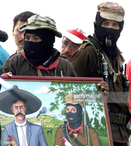 Zapatista leader Subcomandante Marcos watches as an unidentified comrade puts away a painting of himself and Mexican legendary revolutionary Emiliano...