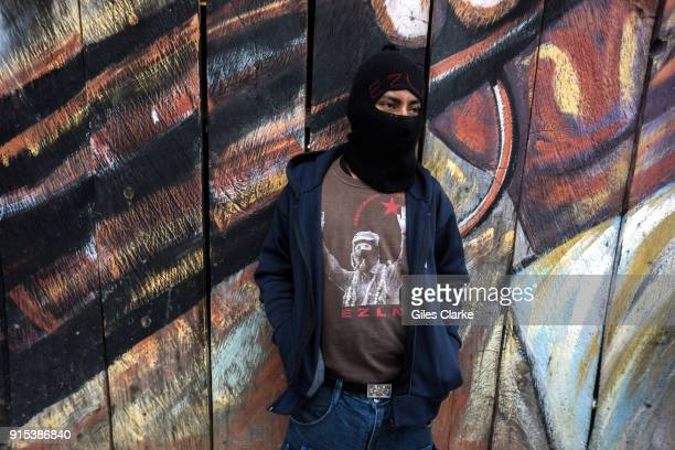 Zapatista man in front of mural in the community of Chiapas The Zapatista Army of National Liberation often referred to as the Zapatistas is a...