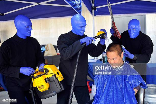 """Zappos.com CEO Tony Hsieh pretends to have his head cut by members of Blue Man Group before the unveiling of the """"ShoeZaphone"""" during the annual Bald..."""