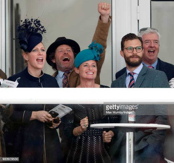 Zara Phillips Dolly Maude and Jamie Dornan watch the racing as they attend day 4 'Gold Cup Day' of the Cheltenham Festival at Cheltenham Racecourse...