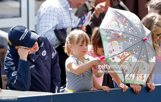 Zara Phillips looks on as daughter Mia Tindall plays with an umbrella on day 2 of the Festival of British Eventing at Gatcombe Park on August 5 2017...
