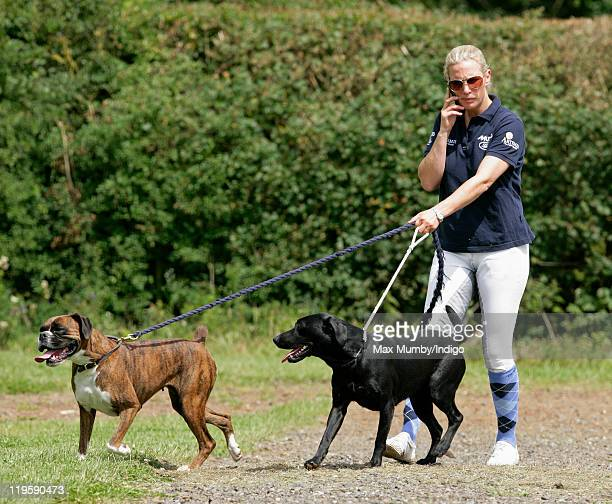 Zara Phillips uses her mobile phone as she walks her dogs around the cross country course during a break from competing in the AstonleWalls Horse...