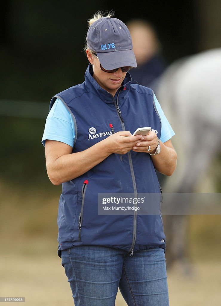 Zara Phillips using her mobile phone as she watches rider Aimee Aspinall compete, on one of Zara's horses, at the Smiths Lawn Horse Trials on August 5, 2013 in Windsor, England.